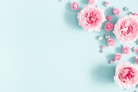 Composizione di fiori. Cornice fatta di fiori di rosa pastello su sfondo blu. San Valentino, festa della mamma, festa della donna, concetto di primavera. Disposizione piana, vista dall'alto, copia spazio