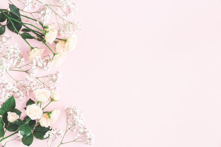Flowers composition. Rose and gypsophila flowers on pastel pink background. Valentines day, mothers day, womens day concept. Flat lay, top view, copy space Stock Photo