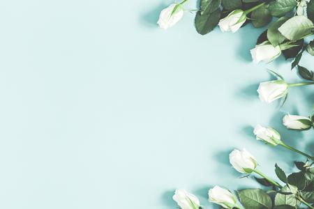Composición de flores. Flores rosas blancas sobre fondo azul pastel. Endecha plana, vista superior, espacio de copia