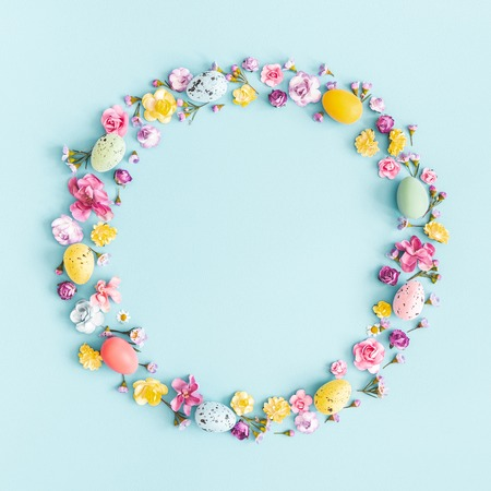 Easter eggs, colorful flowers on pastel blue background. Spring, easter concept. Flat lay, top view, copy space, square Banco de Imagens
