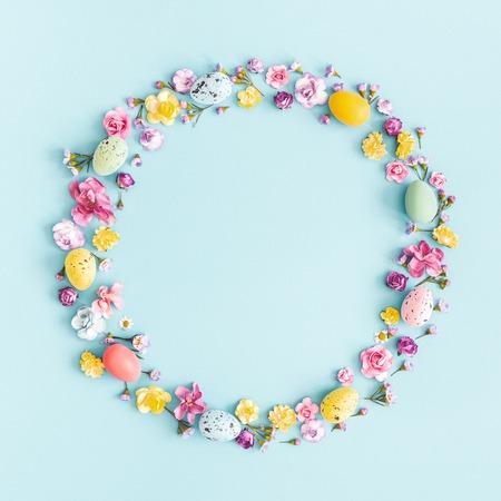 Uova di Pasqua, fiori colorati su sfondo blu pastello. Primavera, concetto di Pasqua. Disposizione piatta, vista dall'alto, copia spazio, quadrato Archivio Fotografico
