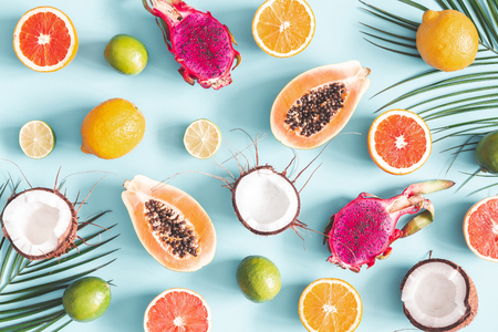 Summer composition. Fruits and palm leaves on pastel blue background. Tropical fruits. Summer concept. Flat lay, top view