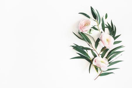 Blumen Zusammensetzung. Rosa Blumen und Eukalyptusblätter auf weißem Hintergrund. Flache Lage, Ansicht von oben, Kopienraum Standard-Bild