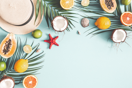 Summer composition. Tropical palm leaves, hat, fruits on pastel blue background. Summer concept. Flat lay, top view, copy space