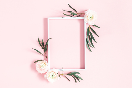 Composición de flores. Flores blancas, hojas de eucalipto, marco de fotos sobre fondo rosa pastel. Endecha plana, vista superior, espacio de copia
