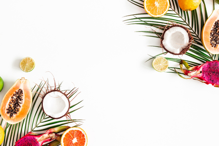 Fruits and palm leaves on white background. Tropical fruits. Summer concept. Flat lay, top view, copy space