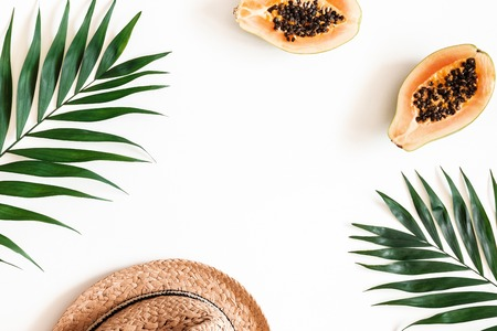 Summer composition. Tropical palm leaves, hat, fruits on white background. Summer concept. Flat lay, top view, copy space