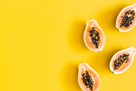 Papaya on yellow background. Summer concept. Flat lay, top view, copy space Stockfoto