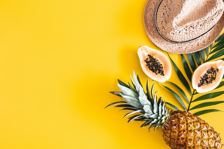 Summer composition. Tropical palm leaves, hat, fruits on yellow background. Summer concept. Flat lay, top view, copy space