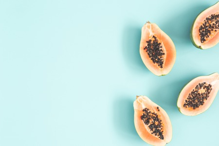Papaya on blue background. Summer concept. Flat lay, top view, copy space