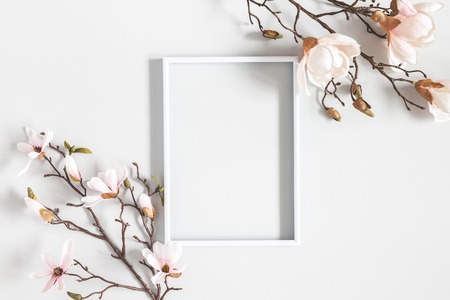 Flowers composition. Magnolia flowers, photo frame on pastel gray background. Flat lay, top view, copy space