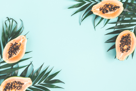 Summer fruits. Papaya and tropical leaves on blue background. Summer concept. Flat lay, top view, copy space