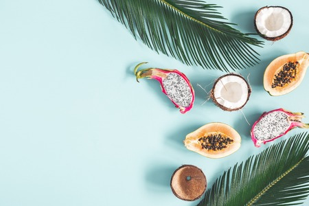 Summer composition. Tropical palm leaves, fruits on blue background. Summer concept. Flat lay, top view, copy space