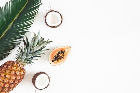 Composizione estiva. Foglie di palma tropicale, frutti su sfondo bianco. concetto di estate. Disposizione piana, vista dall'alto, copia spazio