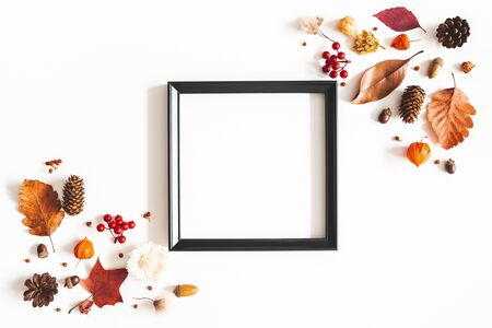 Autumn composition. Photo frame, flowers, leaves on white background. Autumn, fall, thanksgiving day concept. Flat lay, top view, copy space Фото со стока