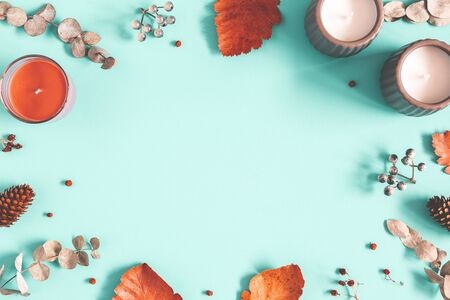 Autumn composition. Candles, scarf, leaves on pastel blue background. Autumn, fall, winter concept. Flat lay, top view, copy space