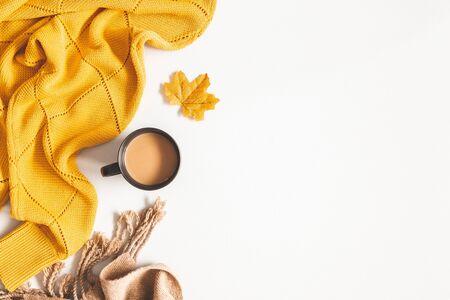 Herfst compositie. Kopje koffie, gele trui, plaid op witte achtergrond. Herfst, herfstconcept. Platliggend, bovenaanzicht, kopieerruimte Stockfoto