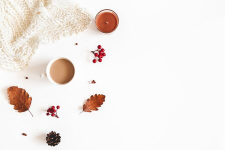 Autumn composition. Cup of coffee, plaid, dried leaves, flowers, rowan berries on white background. Autumn, fall, thanksgiving day concept. Flat lay, top view, copy space