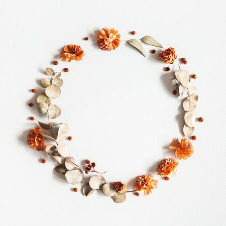Autumn composition. Wreath made of dried flowers, eucalyptus leaves, berries on gray background. Autumn, fall, thanksgiving day concept. Flat lay, top view, copy space, square Standard-Bild