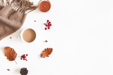 Autumn composition. Cup of coffee, scarf, dried leaves, flowers, rowan berries on white background. Autumn, fall, thanksgiving day concept. Flat lay, top view, copy space 写真素材