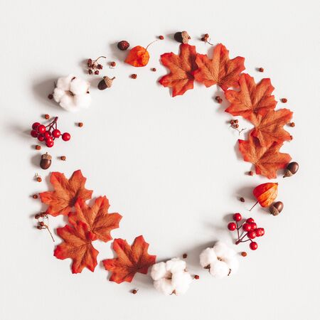 Autumn composition. Wreath made of flowers, maple leaves on gray background. Autumn, fall, thanksgiving day concept. Flat lay, top view, copy space