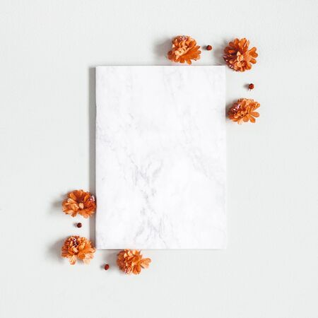 Autumn composition. Paper blank, flowers, leaves on gray background. Autumn, fall, thanksgiving day concept. Flat lay, top view, copy space