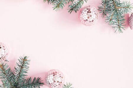 Christmas composition. Frame made of fir tree branches, pink balls on pastel pink background. Christmas, winter, new year concept. Flat lay, top view, copy space Stock Photo