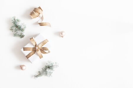 Christmas composition. Gift, fir tree branches, balls on white background. Christmas, winter, new year concept. Flat lay, top view, copy space Stok Fotoğraf