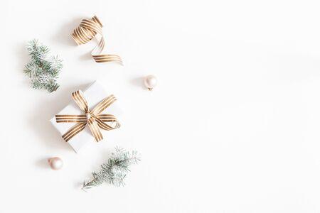 Weihnachtskomposition. Geschenk, Tannenbaumzweige, Kugeln auf weißem Hintergrund. Weihnachten, Winter, Neujahrskonzept. Flache Lage, Ansicht von oben, Kopienraum Standard-Bild
