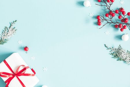Christmas or winter composition. Frame made of gift, snowflakes, fir tree branches and red berries on pastel blue background. Christmas, winter, new year concept. Flat lay, top view, copy space 写真素材