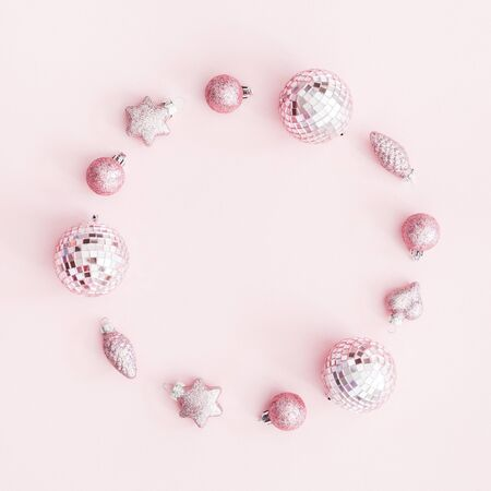 Christmas composition. Wreath made of pink balls on pastel pink background. Christmas, winter, new year concept. Flat lay, top view, copy space, square Stock Photo