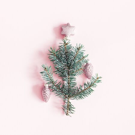 Christmas composition. Fir tree branches, pink decorations on pastel pink background. Christmas, winter, new year concept. Flat lay, top view, square