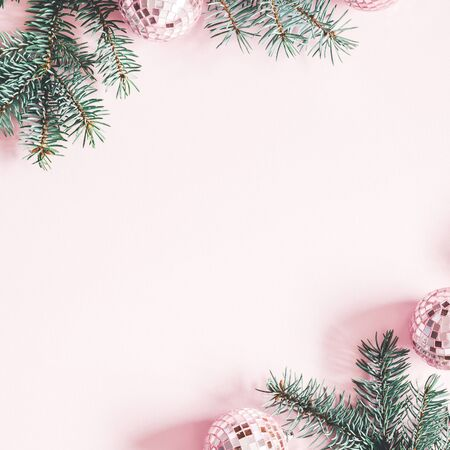 Christmas composition. Frame made of fir tree branches, pink balls on pastel pink background. Christmas, winter, new year concept. Flat lay, top view, copy space, square