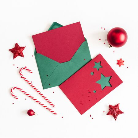 Christmas composition. Envelope, paper card, red decorations on white background. Christmas, winter, new year concept. Flat lay, top view, copy space, square