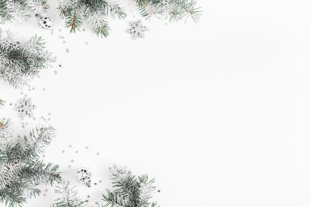 Christmas composition. Frame made of fir tree branches, silver decorations on white background. Christmas, winter, new year concept. Flat lay, top view, copy space