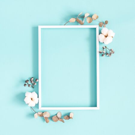 Winter composition. Photo frame, dried leaves, cotton flowers, berries on blue background. Autumn, winter concept. Flat lay, top view, copy space, square