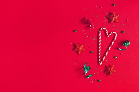 Christmas composition. Pattern made of christmas decorations on red background. Flat lay, top view, copy space