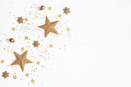 Weihnachtskomposition. Goldene Dekorationen auf weißem Hintergrund. Weihnachten, Winter, Neujahrskonzept. Flache Lage, Ansicht von oben, Kopienraum