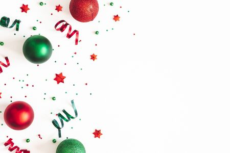 Christmas composition. Red and green decorations on white background. Christmas, winter, new year concept. Flat lay, top view, copy space