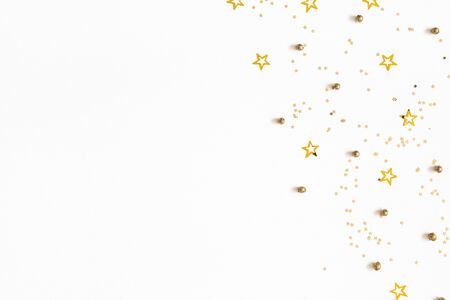 Christmas composition. Christmas golden confetti on white background. Flat lay, top view, copy space