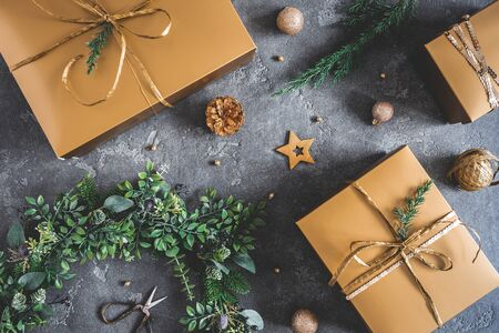 Christmas composition. Gift box, wreath, golden decoration on black background. Christmas, winter, new year concept. Flat lay, top view