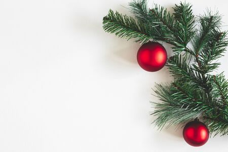 Christmas composition. Fir tree branches, red balls on white background. Christmas, winter, new year concept. Flat lay, top view, copy space