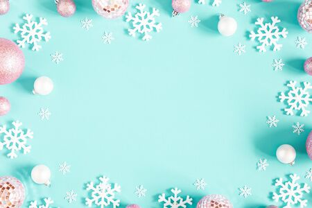 Christmas composition. Frame made of pink balls and white snowflakes on pastel blue background. Christmas, winter, new year concept. Flat lay, top view, copy space