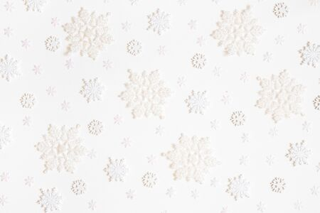Christmas composition. Pattern made of white snowflakes on white background. Christmas, winter, new year concept. Flat lay, top view
