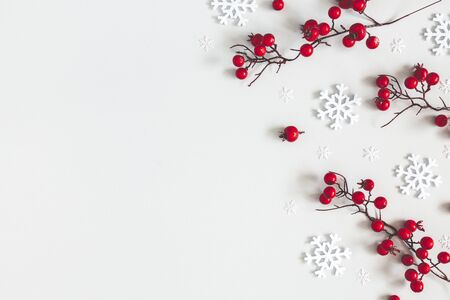 Christmas or winter composition. Snowflakes and red berries on gray background. Christmas, winter, new year concept. Flat lay, top view, copy space Zdjęcie Seryjne
