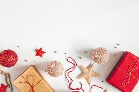 Christmas composition. Gifts, red and golden decorations on gray background. Christmas, winter, new year concept. Flat lay, top view, copy space Zdjęcie Seryjne