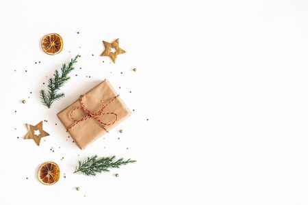 Christmas composition. Gift box, fir tree branches, golden decorations on white background. Christmas, winter, new year concept. Flat lay, top view, copy space Zdjęcie Seryjne