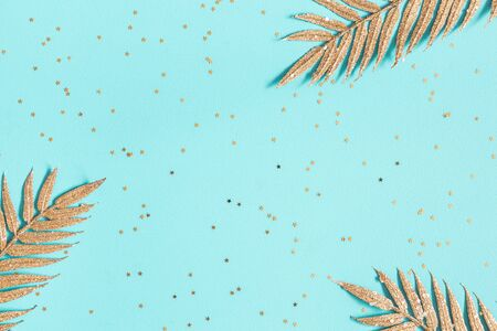 Christmas composition. Golden feathers, confetti on blue background. Christmas, winter, new year concept. Flat lay, top view, copy space Zdjęcie Seryjne