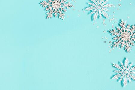 Christmas composition. Silver snowflakes on pastel blue background. Christmas, winter, new year concept. Flat lay, top view, copy space