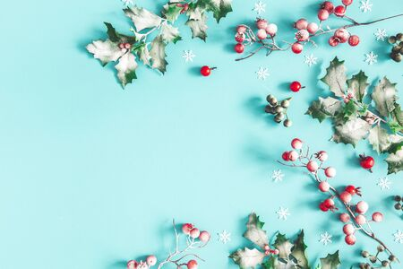 Christmas composition. Frame made of christmas plants on blue background. Flat lay, top view, copy space